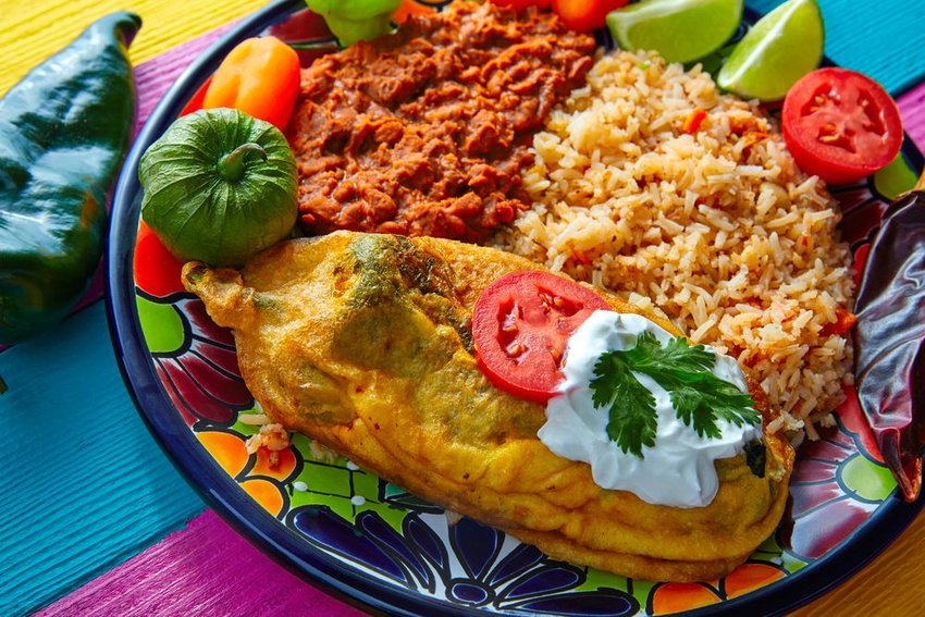 Large chile relleno plate with fried rice, beans, and vegetables