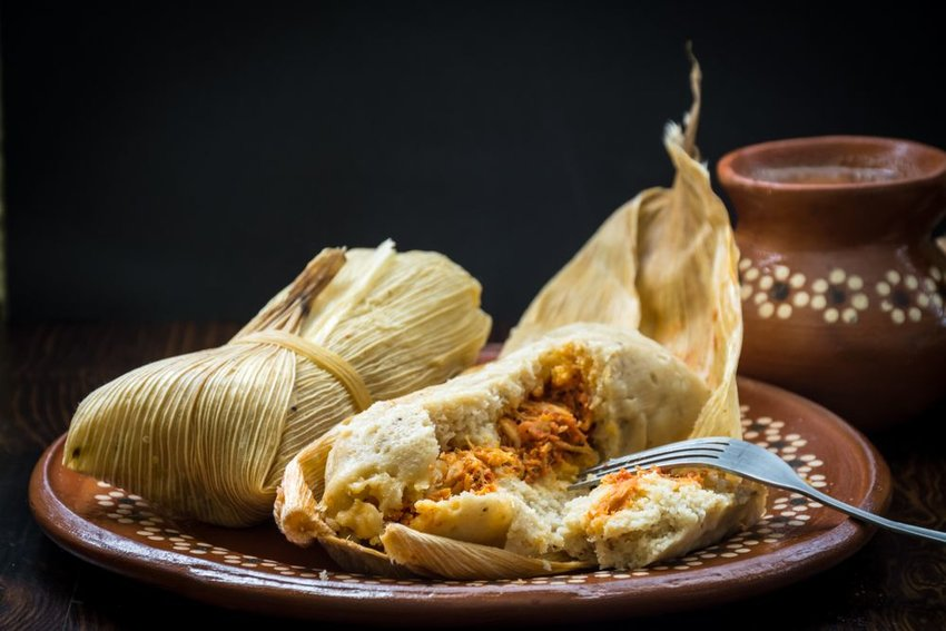 Authentic Mexican tamales being eaten with a fork, served on ceramic plate