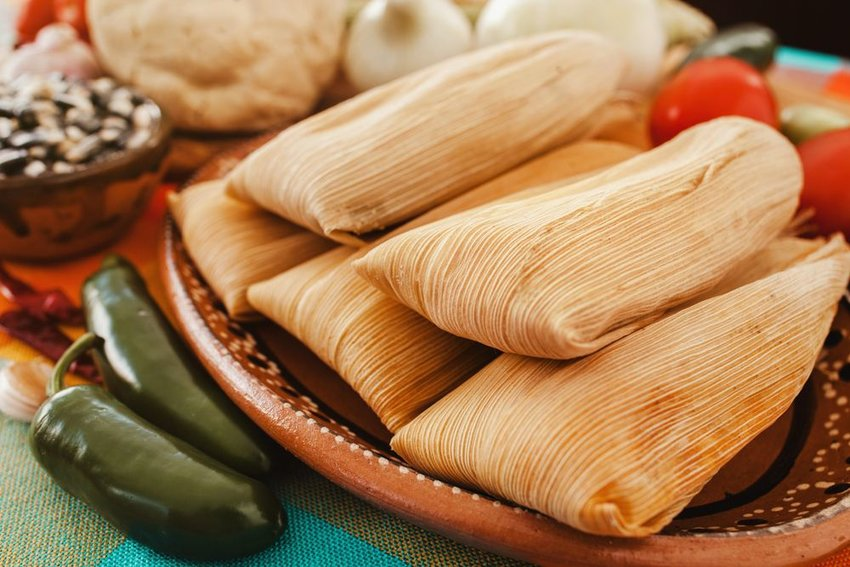 Authentic Mexican tamales wrapped up on plates with peppers and beans