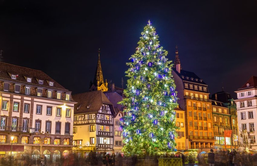 View of the famous Strasbourg Christmas Market lit at night with huge Christmas tree, Alsace, France