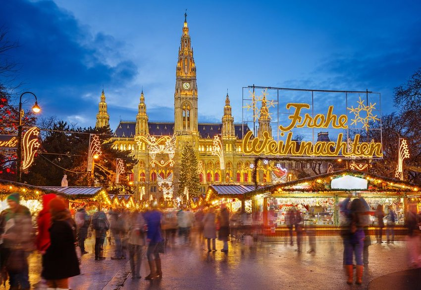 Street view of busy Christmas Market in Vienna, Austria, lit in the evening during sunset