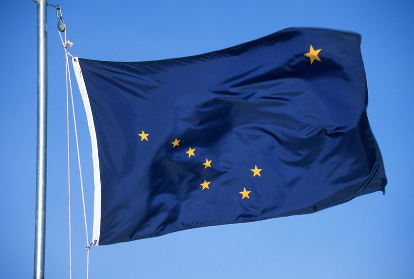 Up close view of Alaskan state flag, with blue background and golden stars arranged in constellation