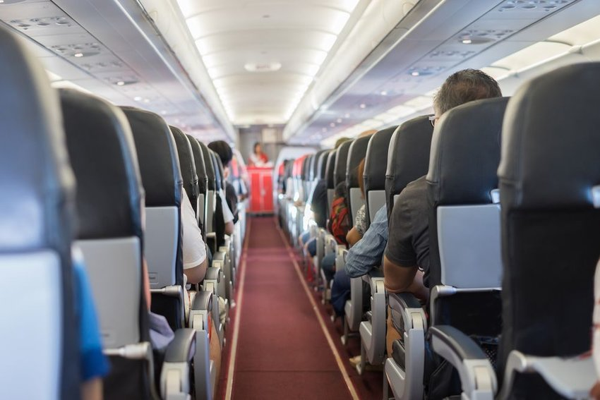 Interior view of commercial airplane with rows of seats and passengers