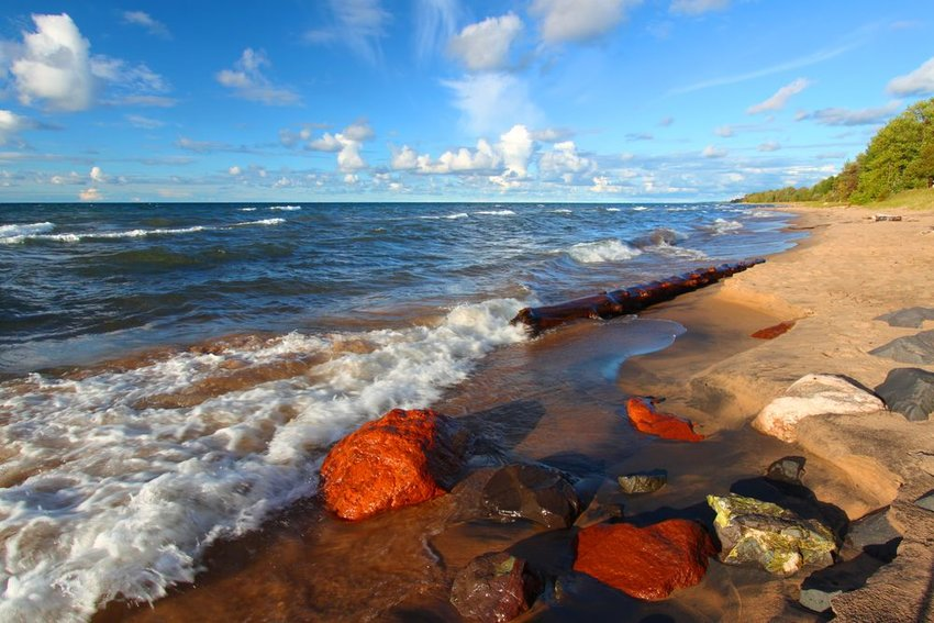 Scenic beach at Lake Superior, showing red rocks, sandy shores, and crashing blue waves