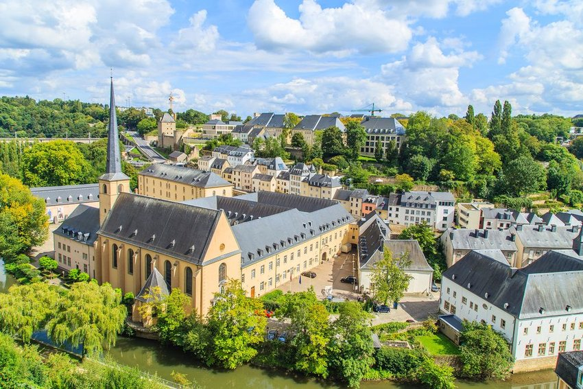 Aerial view of historic city in Luxembourg, showing lush greenery and architecture