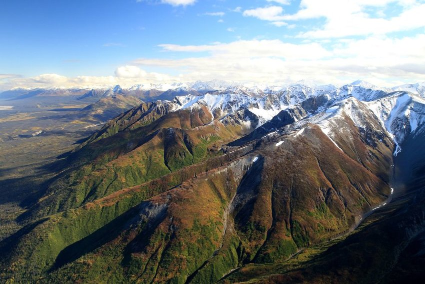 Aerial view of scenic mountain landscape and snow-capped peaks in Wrangell-St. Elias National Park, Alaska