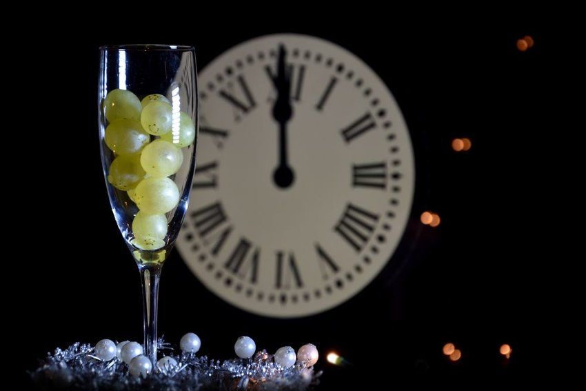 Champagne glass filled with grapes in front of a ticking new year's eve clock