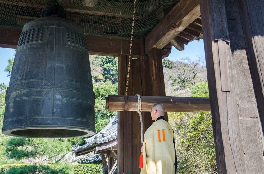 Monk at Japanese temple preparing to ring large bell with beam and rope