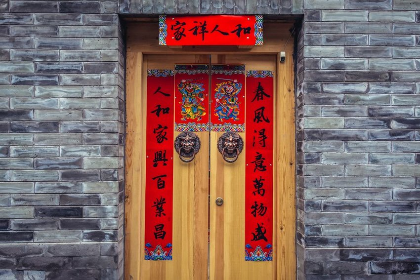 Traditional wooden door adorned in red ornamentation and signage, Beijing, China