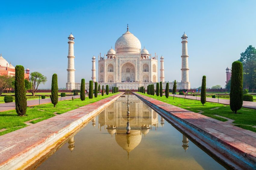 Iconic Taj Mahal mausoleum with tall white pillars and landscape on a clear day, India