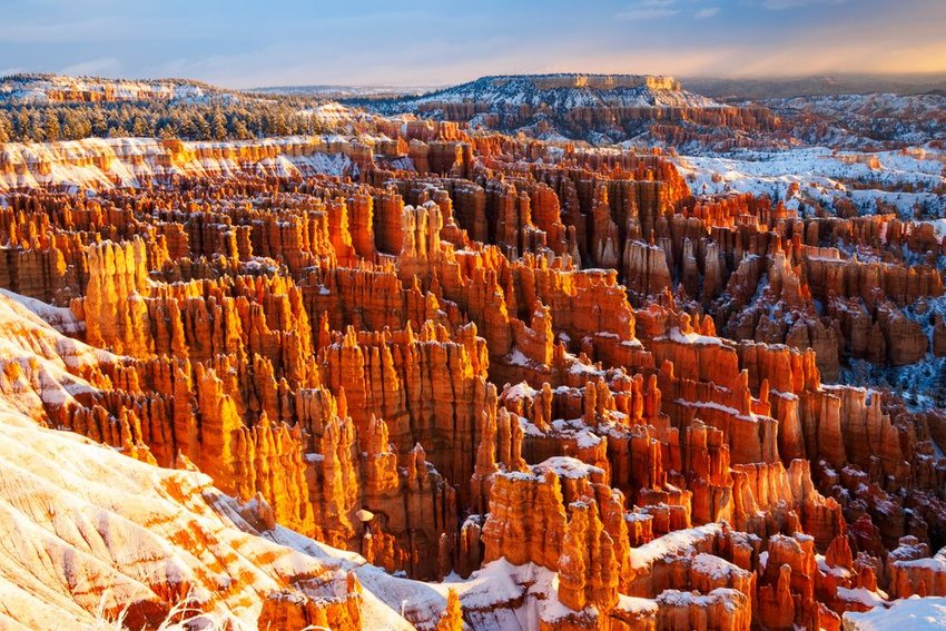 Aerial view of the bright orange rocks in Bryce National Park covered in snow