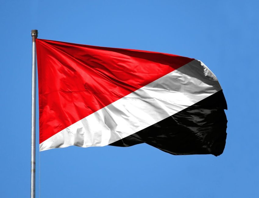 Official Sealand flag with national colors red, white, and black flapping in the wind