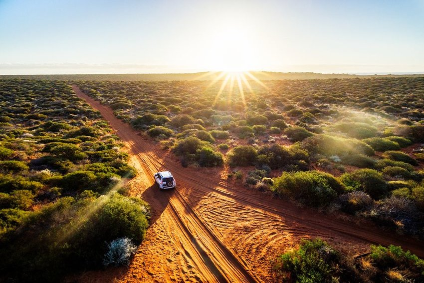 Solitary car driving on dirt road in the Australian Outback as the sun rises