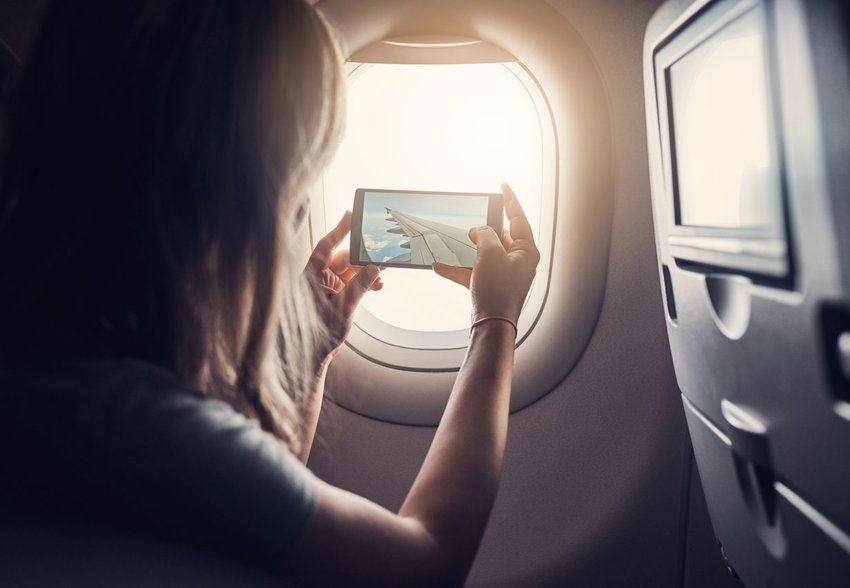 Woman on plane taking photo out the window