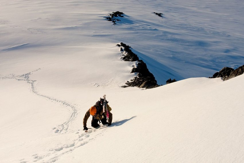 Person climbing up snowy mountain with skis on back to ski down