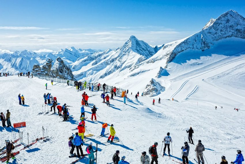 People skiing in Austria with snowy mountain ranges in distance