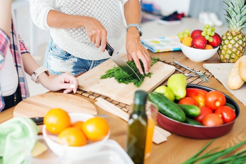People preparing vegetables to cook in kitchen