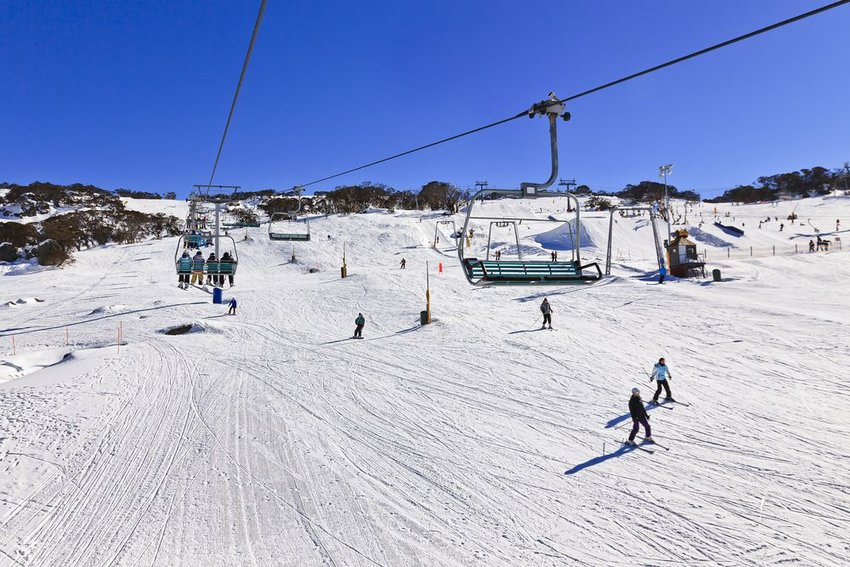 People on chair lift and skiing in Australia