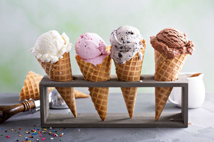 Row of ice cream cones of varying flavors lined up in a cone holder