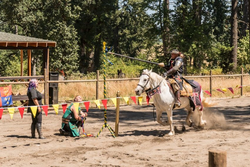 Jousting re-enactment with rider lancing a metal ring on horseback