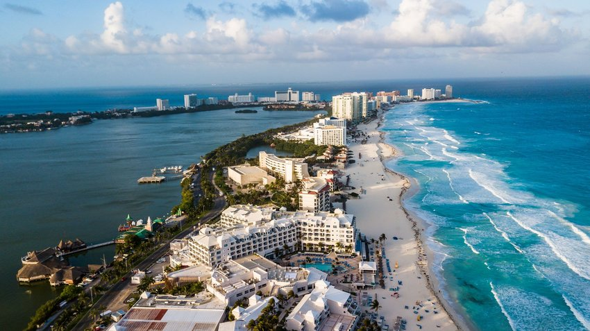 Aerial view of busy Cancun resort with lapping waves against white sandy beaches