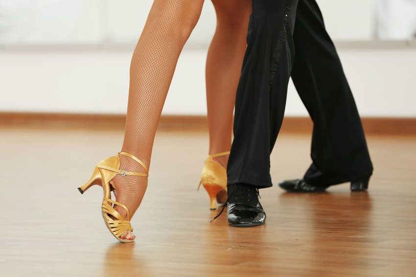 Up close view of man and woman in fancy clothes dancing on wooden floor