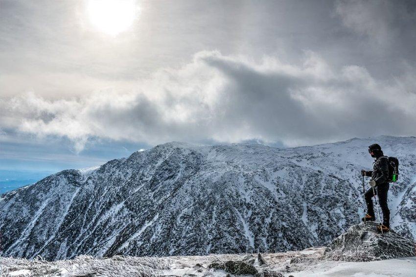 Hiker on the edge of cliff near the peak of snowy Mount Washington, New Hampshire