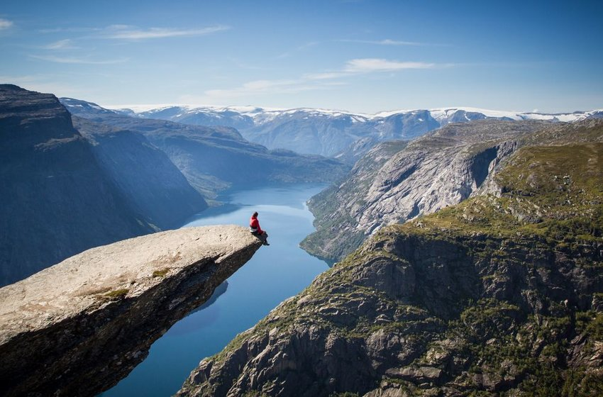 Person sitting on iconic cliffside in Trolltunga, Norway