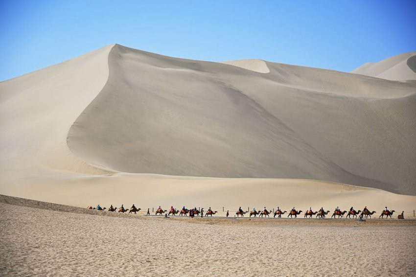 Caravan of travelers on camels move through sweeping sand dunes of the Gobi desert