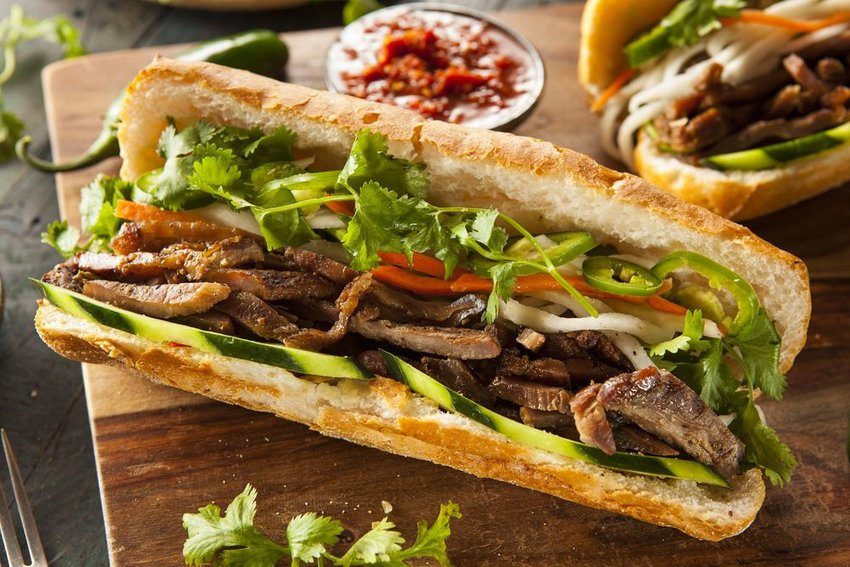 Traditional Banh Mi sandwich on a wooden plank with garnish and seasonings