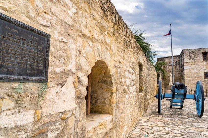 Interior view of Alamo building showing rock walls, antique cannon, and memorial plaque