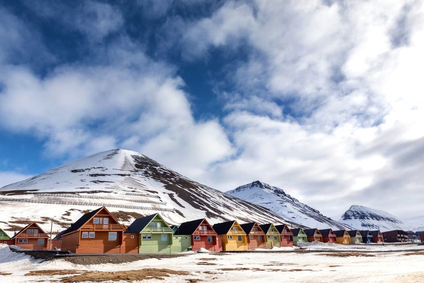 Row of colored homes near large icy mountains in  Longyearbyen, Svalbard