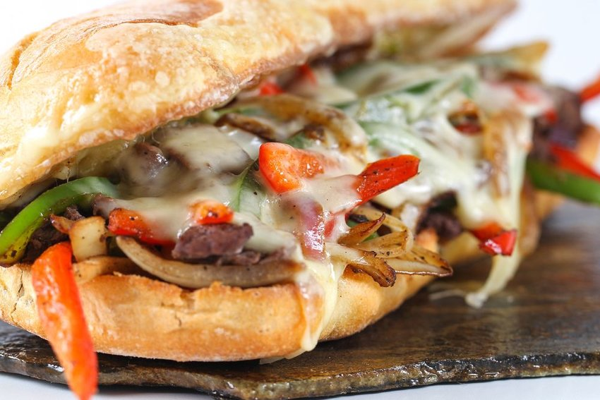Detailed view of cheesesteak sandwich with sliced meat and roasted peppers