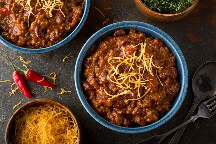 Several large bowls of chili, showing meat and shredded cheese for garnish