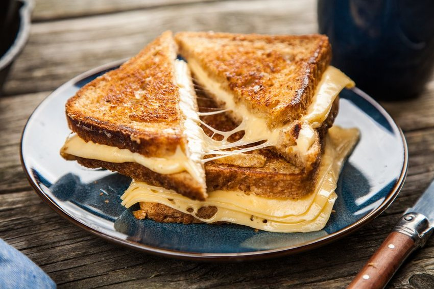 Plate with several grilled cheese sandwiches stacked on top of each other