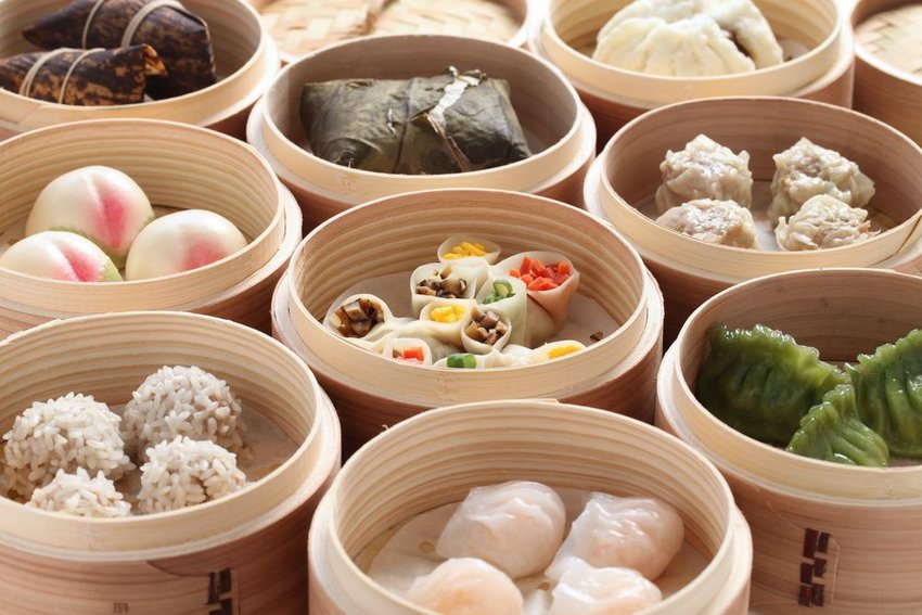 Variety of dim sum dishes in individual bamboo bowls