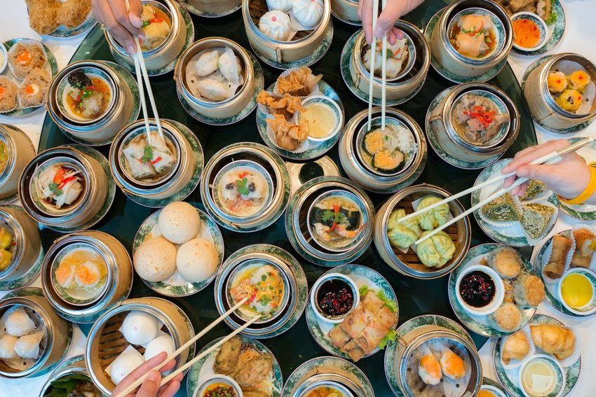 Large variety of colorful dim sum dishes with bowls and chopsticks