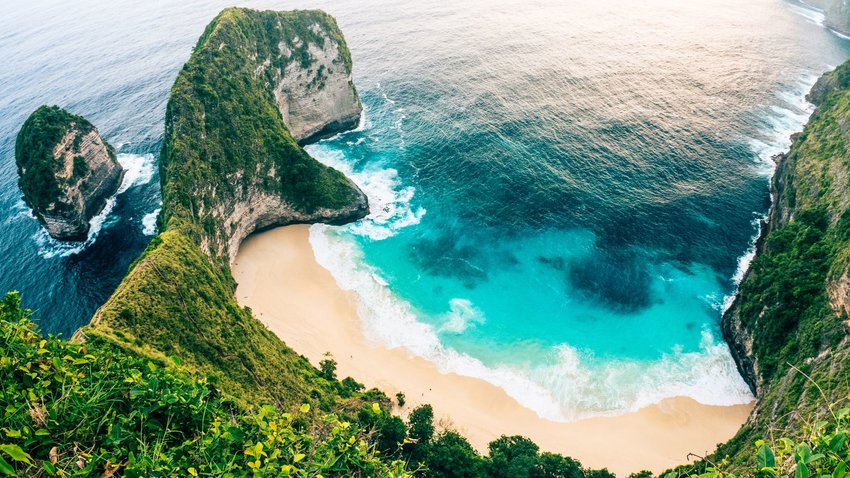 Aerial view of large green cliff and white sand beaches in Bali, Indonesia