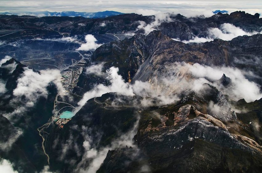 Aerial view of the Grasberg Mine in Papua, showing rolling clouds and rocky peaks