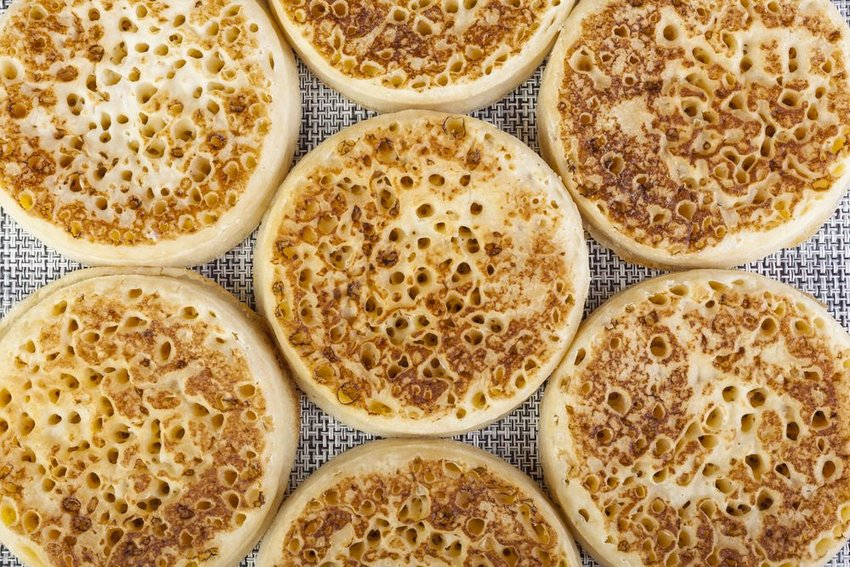 Overhead view of several traditional crumpets with iconic air pockets