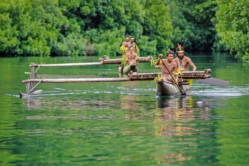 Locals canoe in green waters near Tufi, Oro Province, Papua New Guinea
