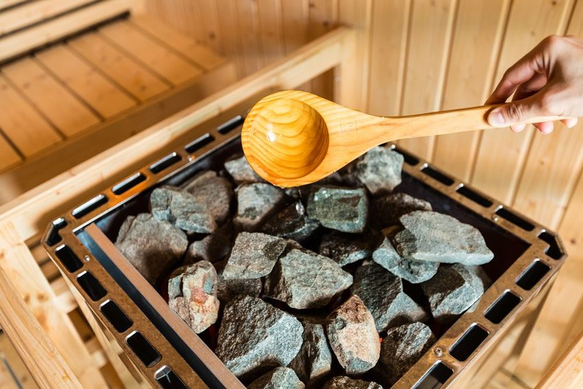 Person's hand pouring water over bin of hot sauna rocks