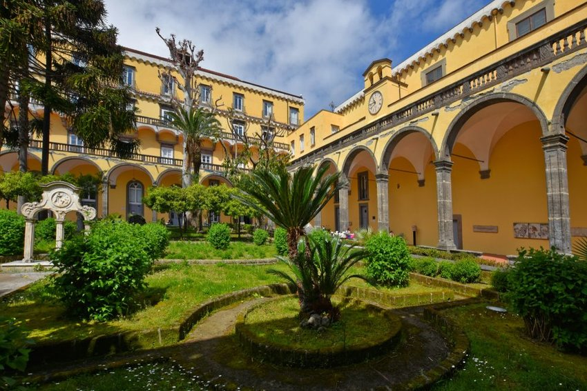 Yellow building with manicured landscape at historic University of Naples, Italy