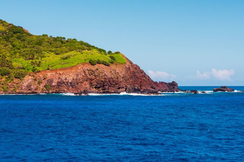 Aerial view of the Pitcairn Island shore with choppy blue waters and red rocks