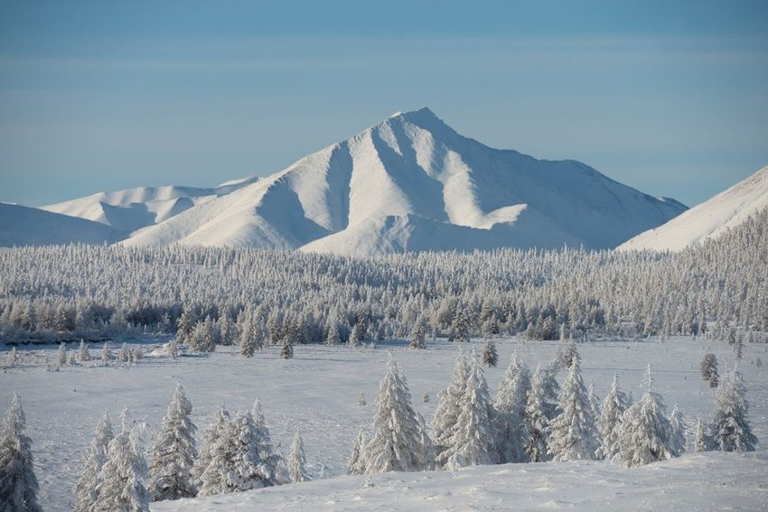 Desolate snowy landscape of Oymyakon, Russia and its large rocky mountains