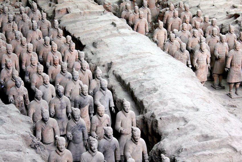 Historic terra-cotta soldier army standing shoulder to shoulder in quarry, China