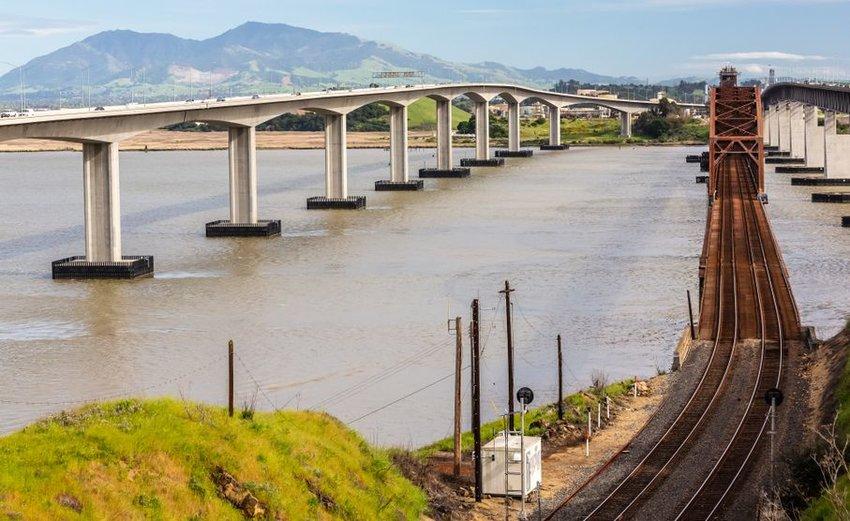 Train tracks going over a bridge next to a car bridge