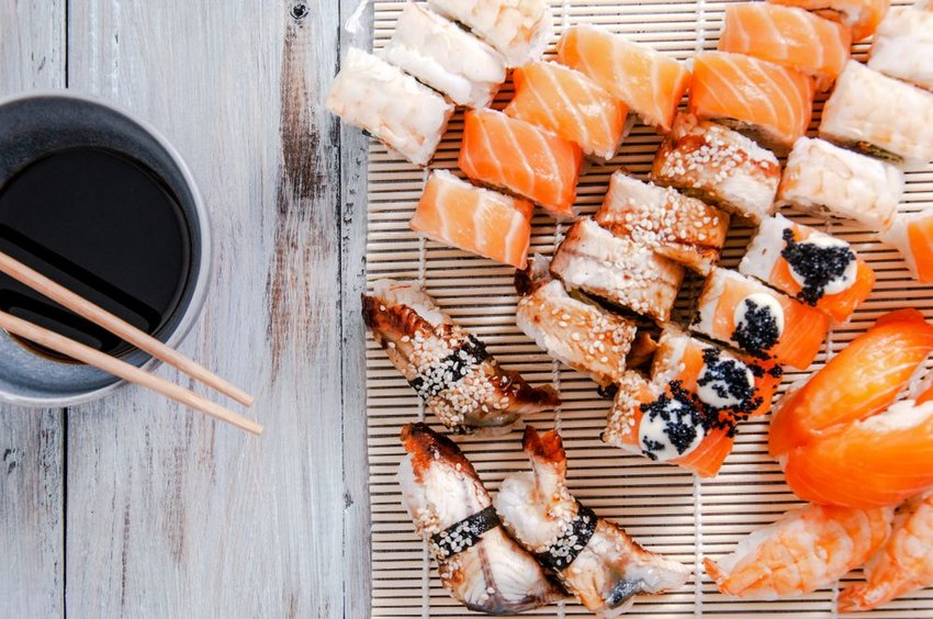 Photo of sushi and chopsticks on a bowl of soy sauce