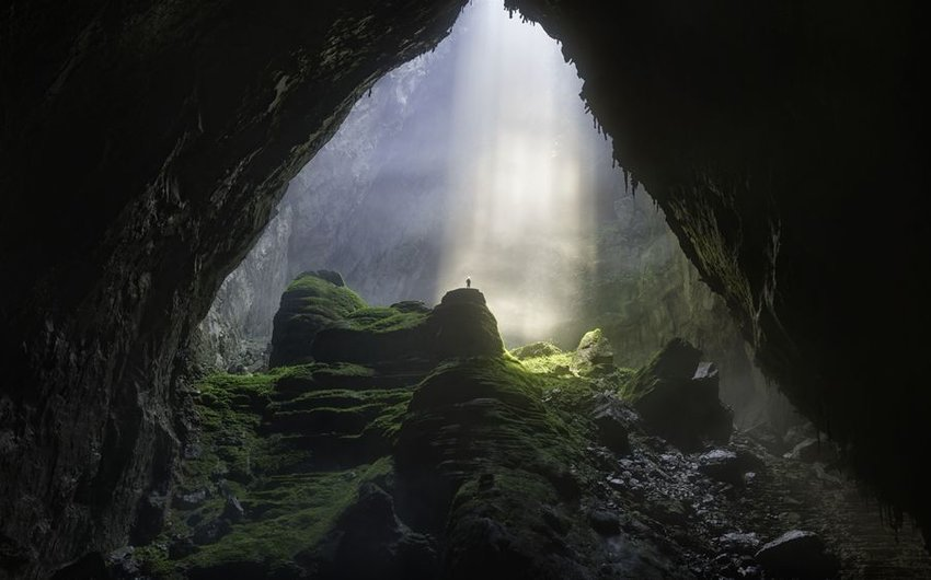 Light streaming into cave from above with person standing in the light