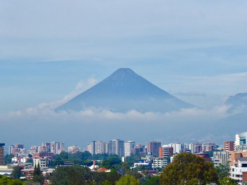 Fuego volcano covered in low clouds with Guatemala city in the foreground